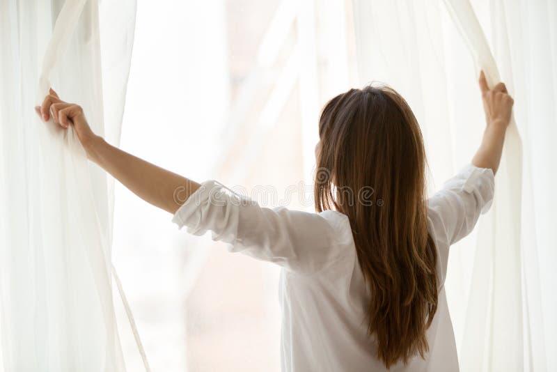 Vista posterior en las cortinas de ventana de abertura de la mujer que disfrutan de buena mañana foto de archivo