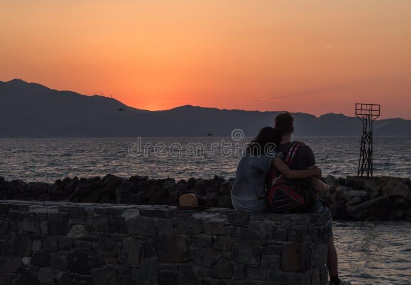 Vista posterior joven de los pares que abraza blando a la muchacha inclinada en el hombro del muchacho que mira la puesta del sol foto de archivo