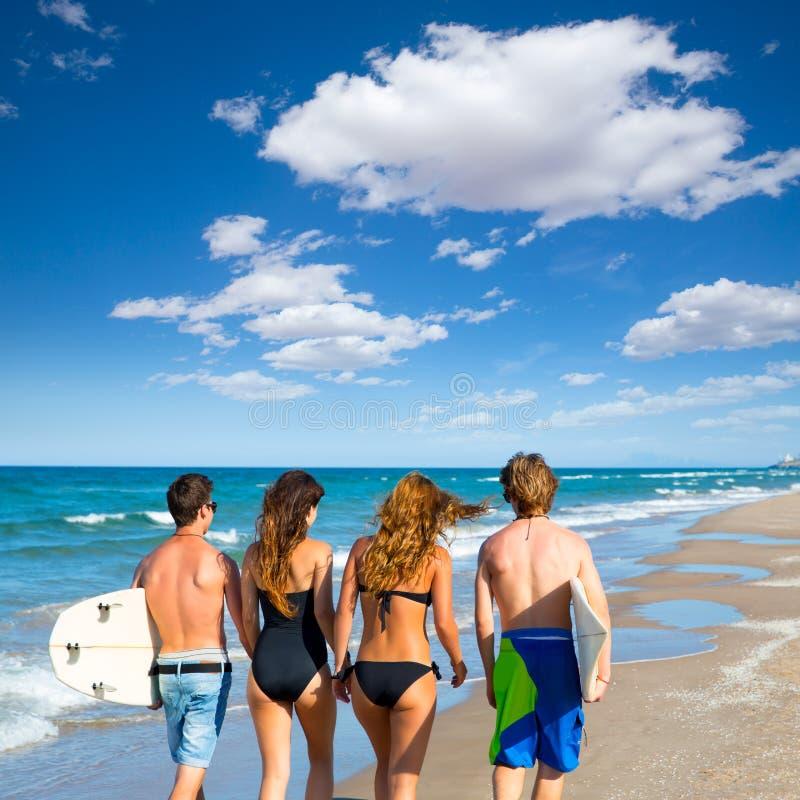 Vista posterior que camina de los muchachos y de las muchachas de las personas que practica surf en la playa imagen de archivo