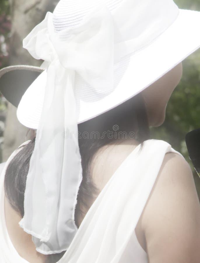 Vista posteriore del cappello bianco da portare della donna graziosa immagine stock