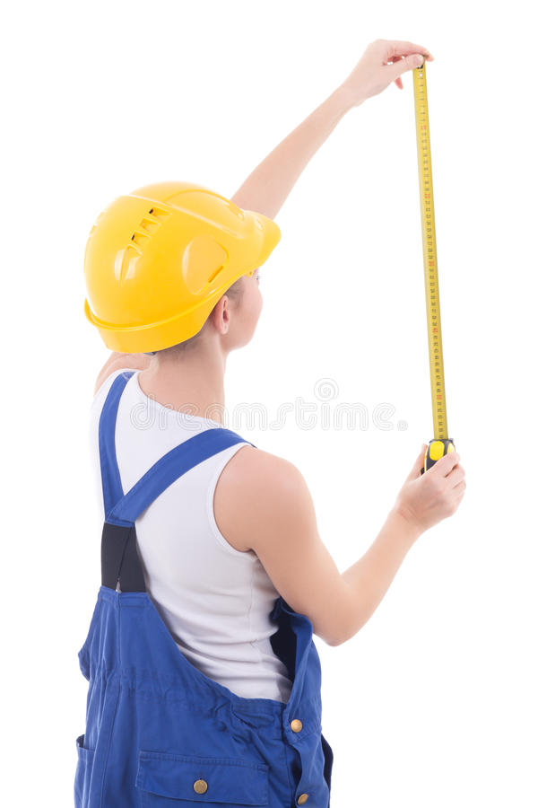 Vista posteriore del costruttore della donna in tute blu che misurano qualcosa fotografia stock