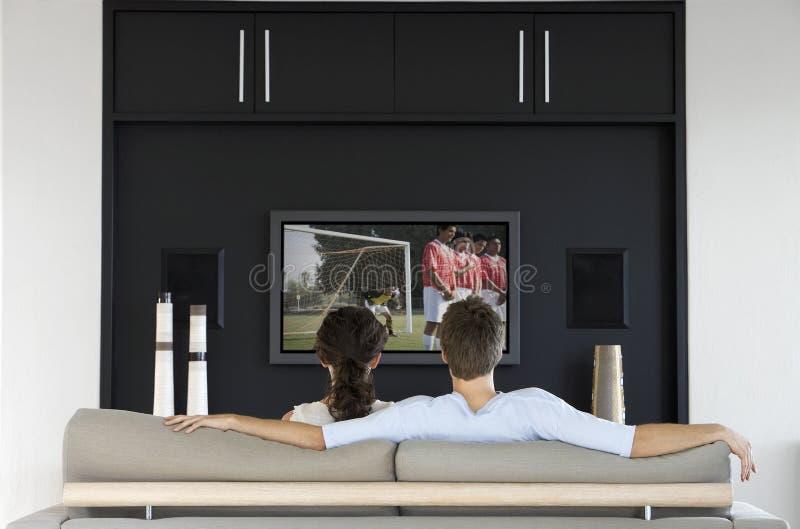 Vista posteriore del gioco di calcio di sorveglianza delle coppie sulla televisione in salone immagine stock libera da diritti