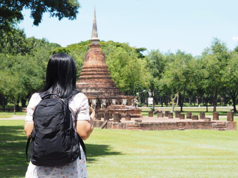 Vista posteriore del viaggiatore con zaino e sacco a pelo asiatico della donna che guarda per rovinare pagoda a ol immagine stock libera da diritti