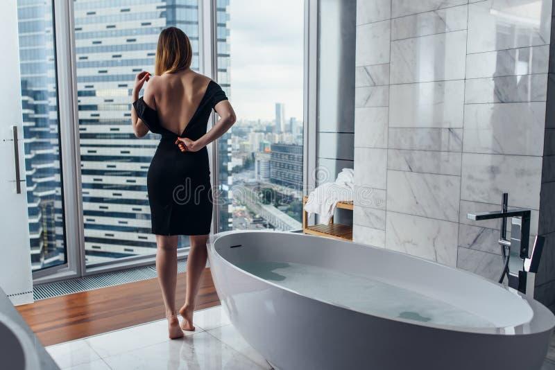 Vista posteriore dell'accappatoio bianco d'uso della giovane donna che sta nel bagno che guarda fuori la finestra con la vasca in immagine stock libera da diritti