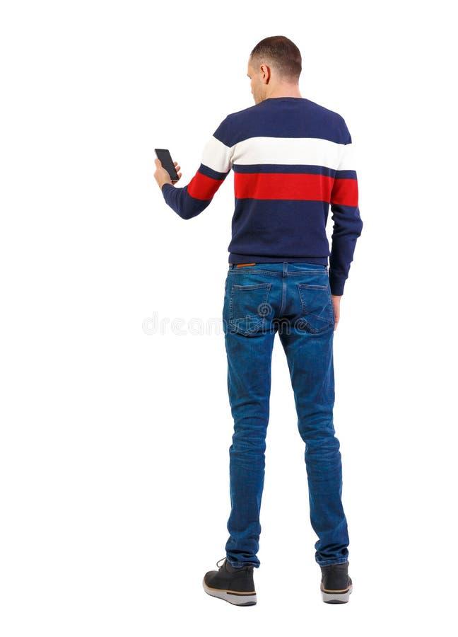 Vista posteriore dell'uomo che sta indagando sullo smartphone immagini stock libere da diritti