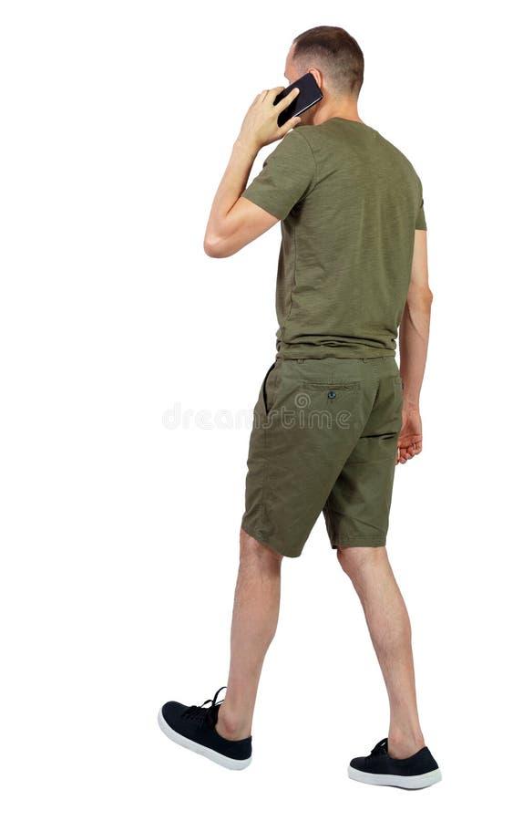 Vista posteriore dell'uomo in pantaloncini che cammina con un cellulare fotografia stock libera da diritti