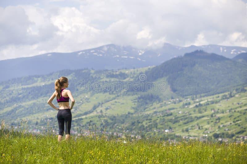 Vista posteriore della condizione esile della giovane donna sulla valle erbosa su fondo delle montagne verdi il giorno di estate  immagini stock