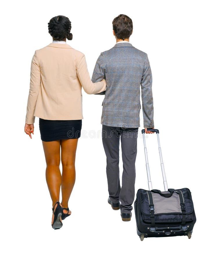 Vista posteriore della coppia interrazziale con valigia immagini stock libere da diritti