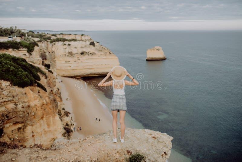 Vista posteriore della giovane donna in cappello e della condizione sveglia del vestito da estate sulla pietra, esaminante tramon fotografia stock libera da diritti