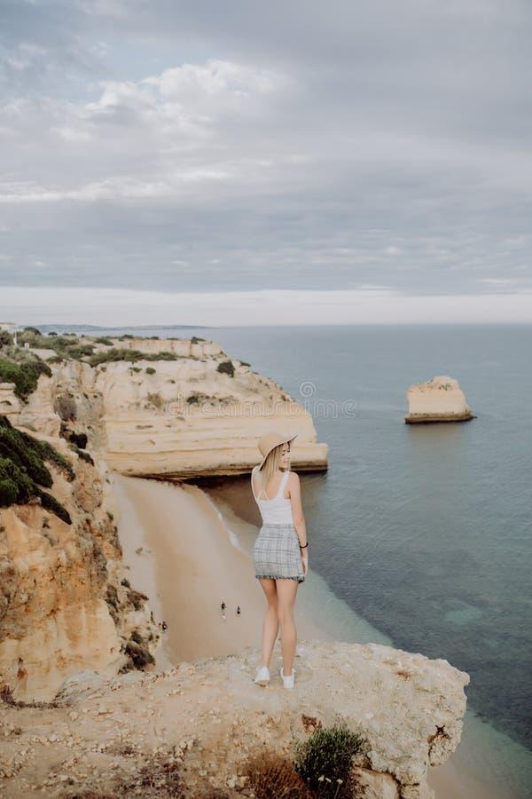 Vista posteriore della giovane donna in cappello e della condizione sveglia del vestito da estate sulla pietra, esaminante tramon fotografia stock