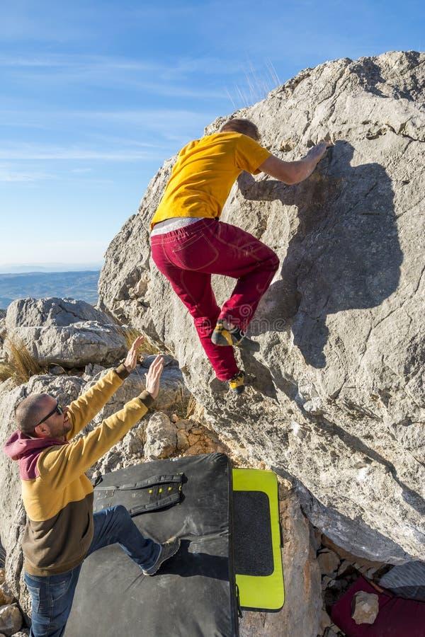 Vista posteriore della roccia rampicante dell'uomo che bouldering fotografia stock libera da diritti
