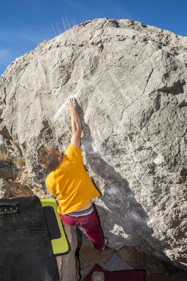 Vista posteriore della roccia rampicante dell'uomo che bouldering fotografie stock libere da diritti