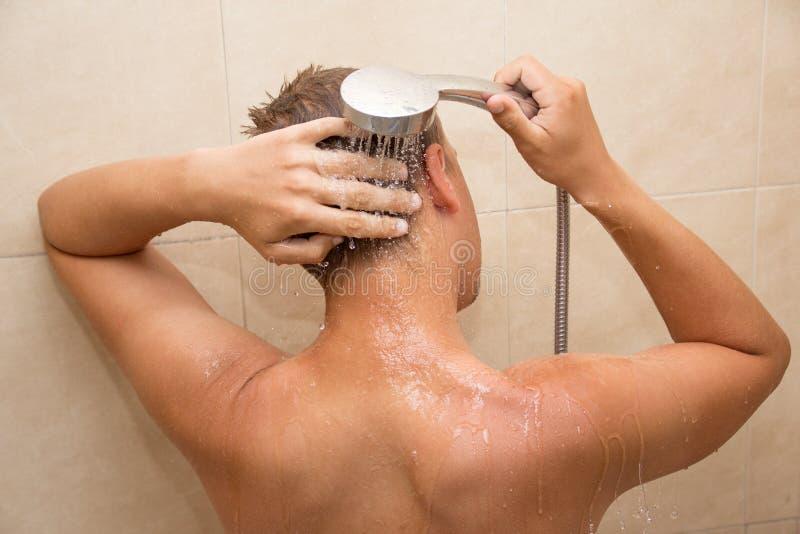 Vista posteriore della testa di lavaggio del giovane in bagno fotografie stock libere da diritti