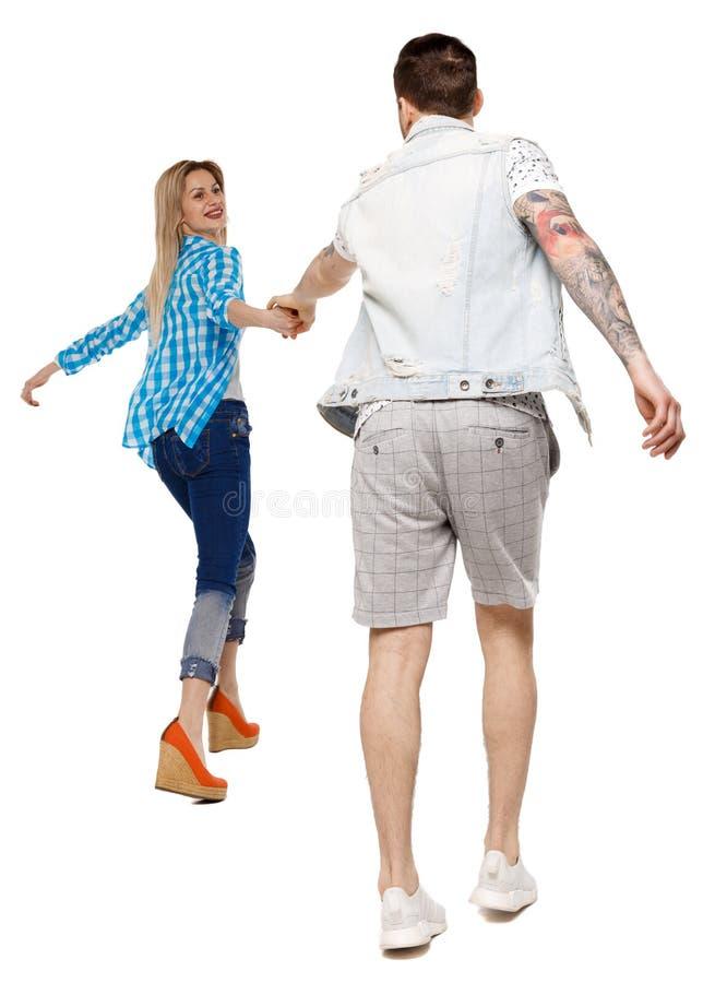 Vista posteriore delle coppie andanti tenersi per mano amichevole di camminata del tipo e della ragazza fotografia stock