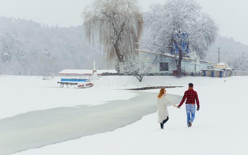Vista posteriore delle coppie felici che si tengono per mano durante la loro passeggiata lungo il paesaggio nevoso Tempo di natal fotografie stock