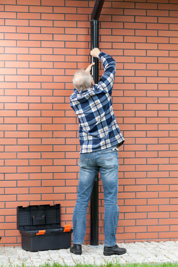 Vista posteriore delle grondaie di una riparazione dell'uomo immagini stock libere da diritti