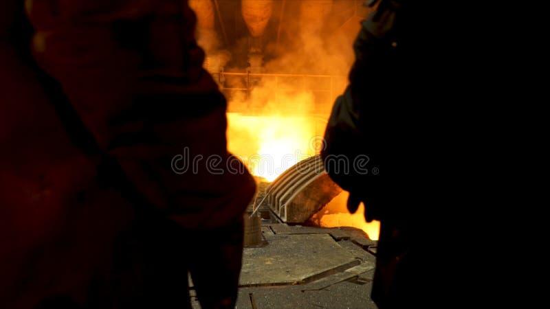 Vista posteriore di due acciaierie della ingot casting davanti al forno elettrico ad arco in un'officina, metallurgica immagini stock