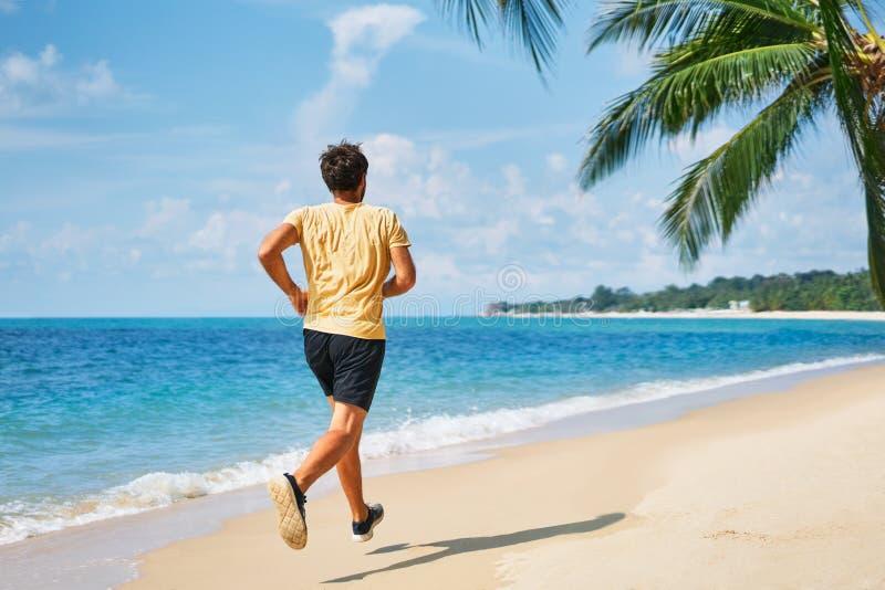 Vista posteriore di eseguire uomo sulla spiaggia tropicale fotografie stock