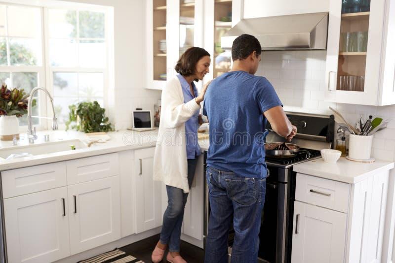 Vista posteriore di giovane condizione delle coppie nella cucina che prepara insieme alimento immagini stock libere da diritti