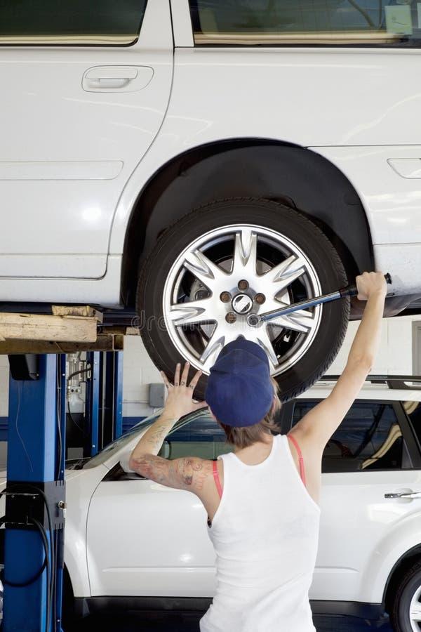 Vista posteriore di giovane lavorare femminile alla gomma di automobile in officina immagine stock