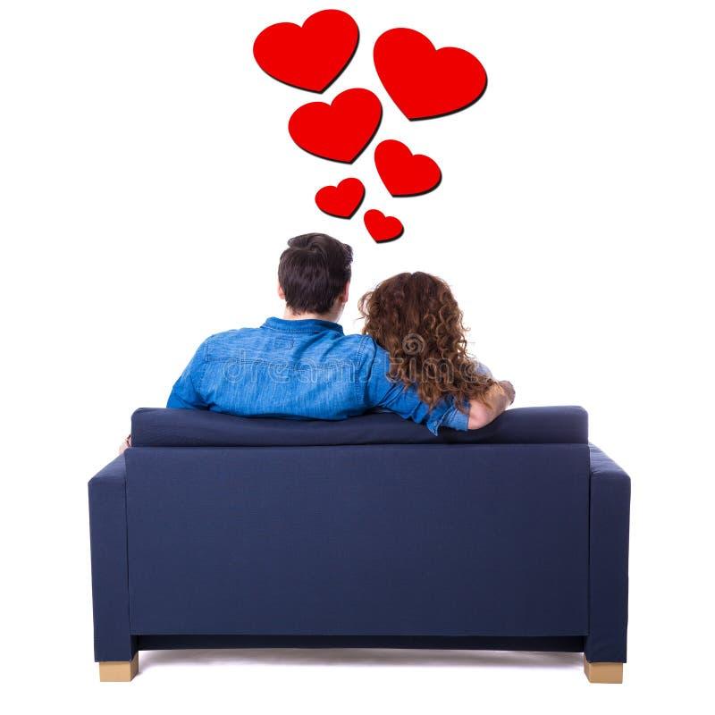 Vista posteriore di giovani coppie adorabili che si siedono sul sofà isolato sul whi immagini stock libere da diritti
