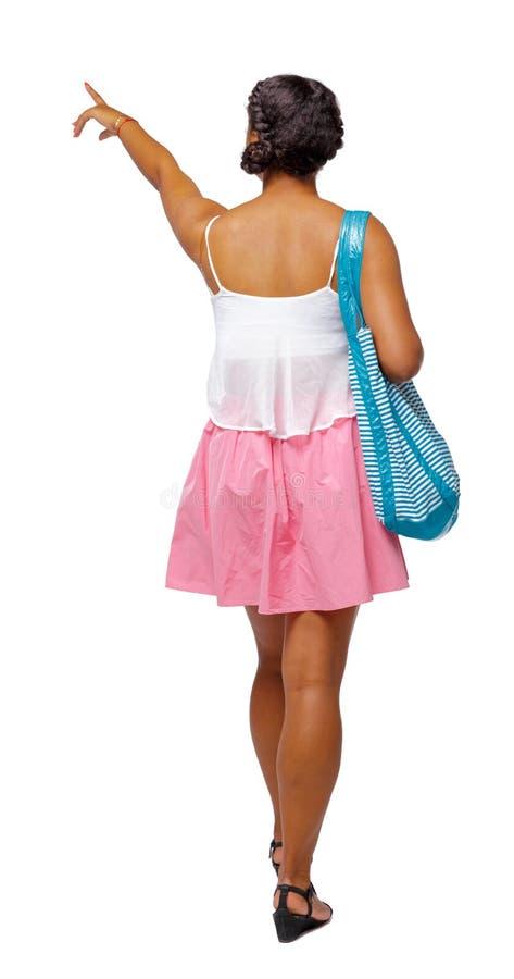 Vista posteriore di indicare afroamericano con una borsa della spiaggia che va al lato fotografia stock libera da diritti