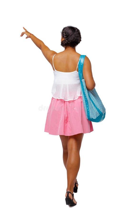 Vista posteriore di indicare afroamericano con una borsa della spiaggia che va al lato fotografie stock