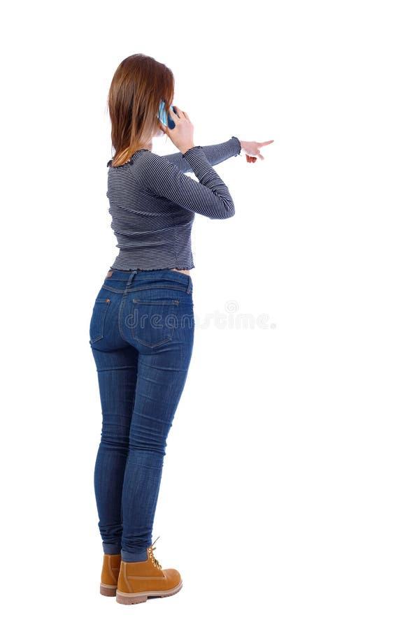 Vista posteriore di indicare le giovani donne che parlano sul telefono cellulare fotografia stock