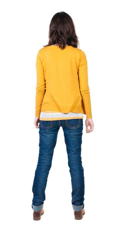Vista posteriore di stare giovane bella donna castana nel giallo immagini stock