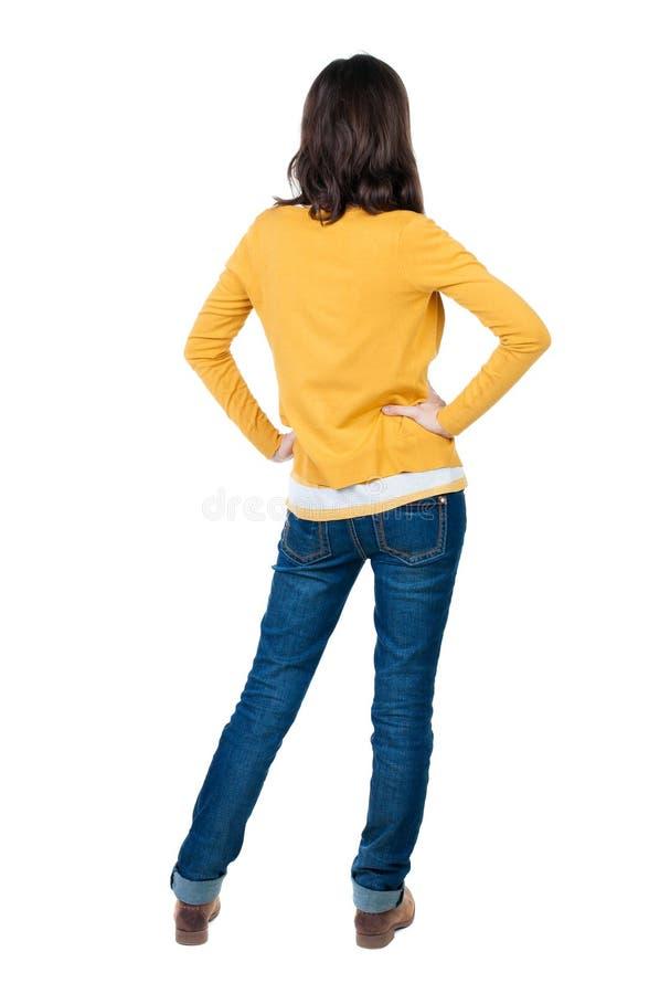 Vista posteriore di stare giovane bella donna castana nel giallo fotografia stock libera da diritti