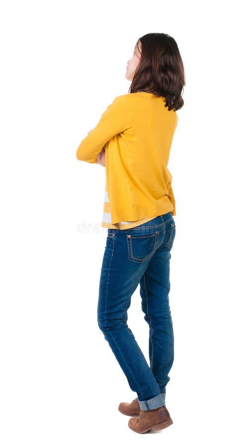 Vista posteriore di stare giovane bella donna castana nel giallo immagine stock libera da diritti
