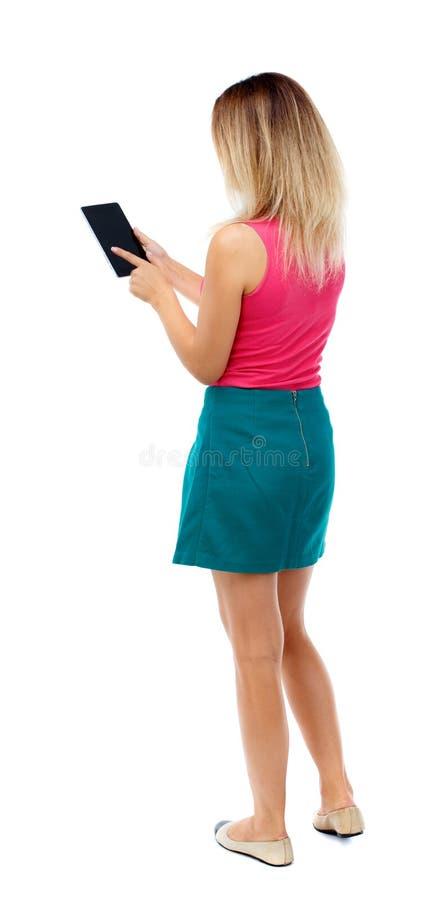 Vista posteriore di stare giovane bella donna che usando un fon mobile immagine stock libera da diritti