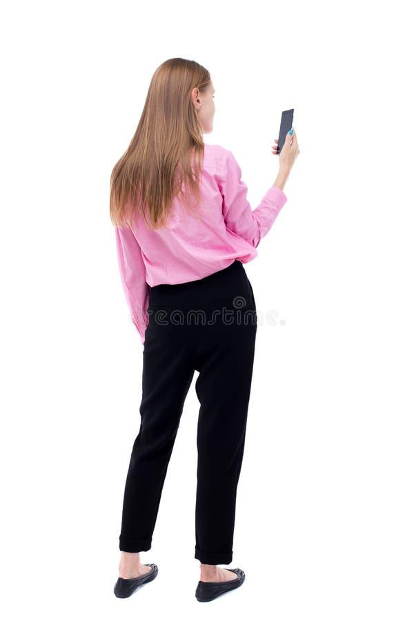 Vista posteriore di stare giovane bella donna e di usando un cellulare fotografie stock