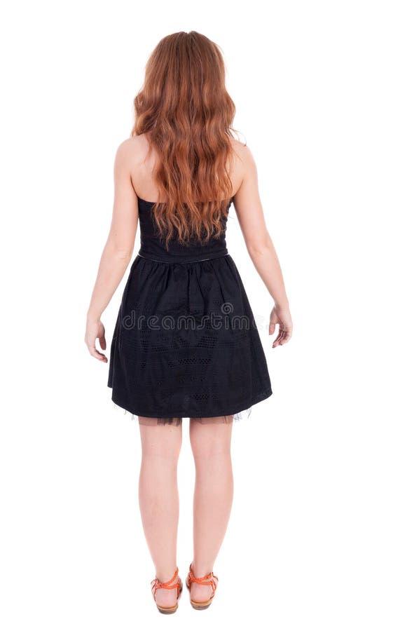 Vista posteriore di stare la giovane bella donna della testarossa immagine stock