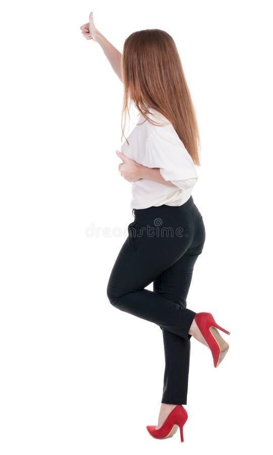Vista posteriore di stare la giovane donna di affari della testarossa che mostra pollice fotografie stock