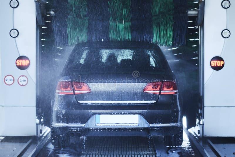 Vista posteriore di un autolavaggio che pulisce un'automobile con le spazzole giranti fotografia stock libera da diritti