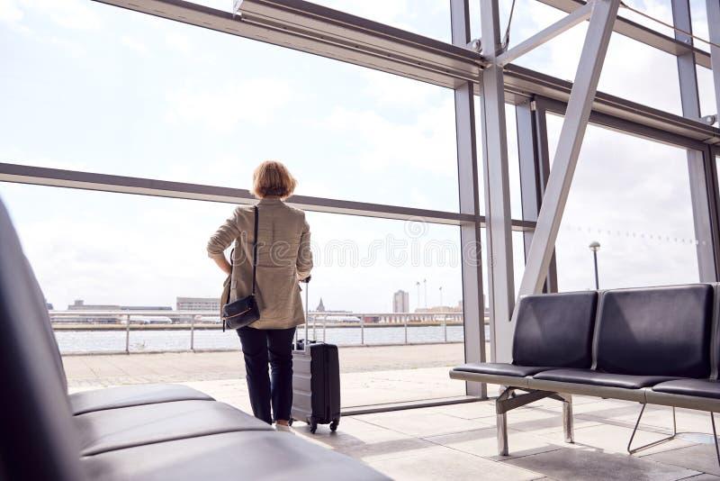 Vista Posteriore Di Un'Imprenditrice Con Bagaglio In Piedi Per Finestra Nel Bocchetto Di Partenza Aeroportuale fotografie stock