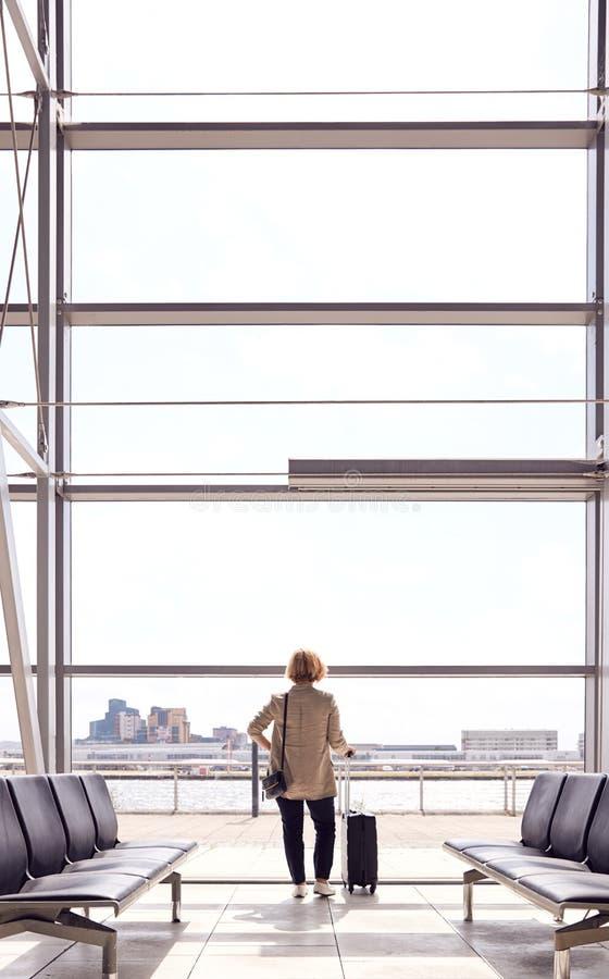 Vista Posteriore Di Un'Imprenditrice Con Bagaglio In Piedi Per Finestra Nel Bocchetto Di Partenza Aeroportuale immagine stock libera da diritti