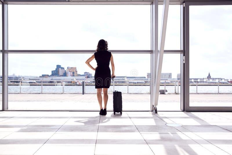 Vista Posteriore Di Un'Imprenditrice Con Bagaglio In Piedi Per Finestra Nel Bocchetto Di Partenza Aeroportuale immagini stock