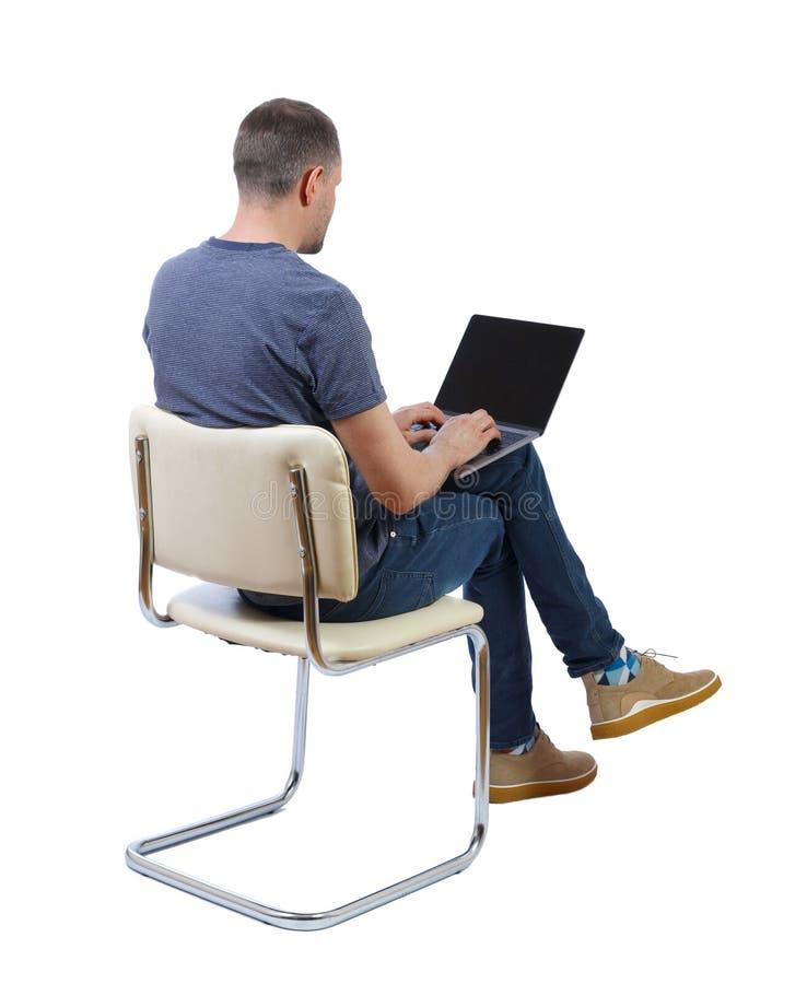 Vista posteriore di un uomo seduto su una sedia con un portatile fotografia stock