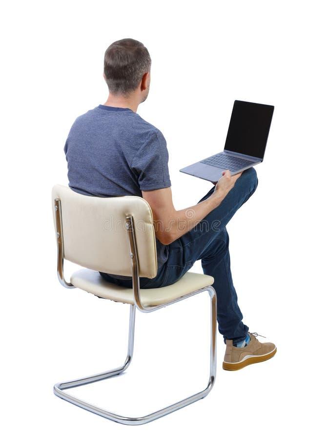 Vista posteriore di un uomo seduto su una sedia immagine stock