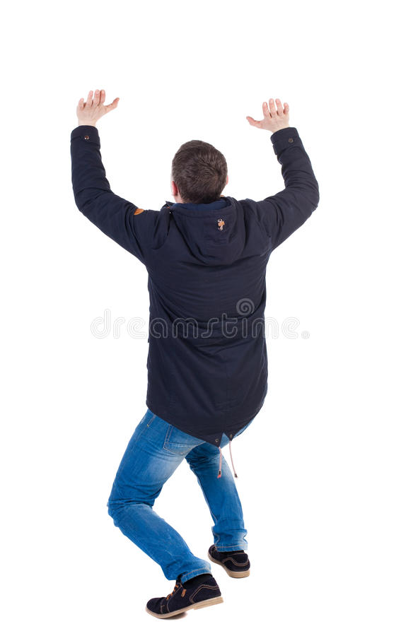 Vista posteriore l'uomo in parka protegge le mani da cui sta cadendo per immagini stock
