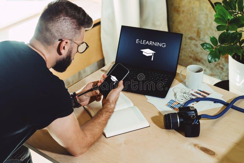 Vista posteriore L'uomo si siede la casa alla tavola, lavora al computer con l'e-learning dell'iscrizione sul monitor Sorveglianz immagini stock