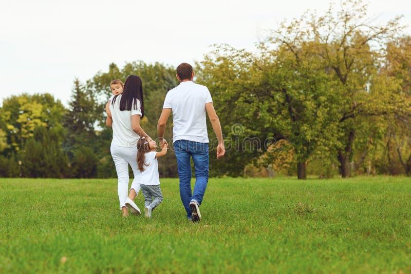 Vista posteriore La famiglia con i bambini cammina nel parco immagine stock