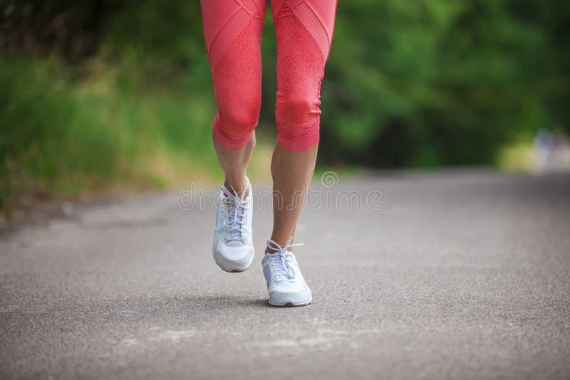 Vista potata di funzionamento dell'atleta della donna sulla via in parco immagini stock libere da diritti