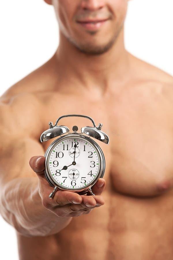 Vista potata di un orologio muscolare della tenuta del giovane fotografie stock libere da diritti