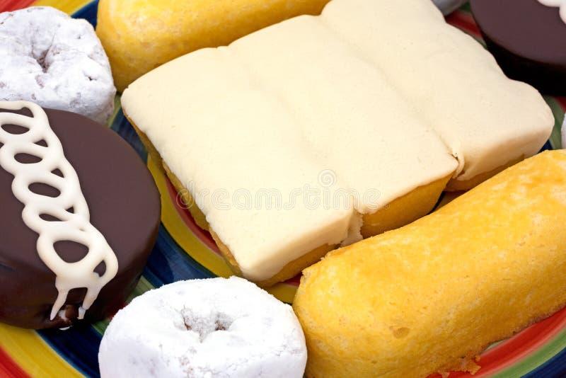 Vista próxima de bolos e de anéis de espuma da comida lixo imagem de stock