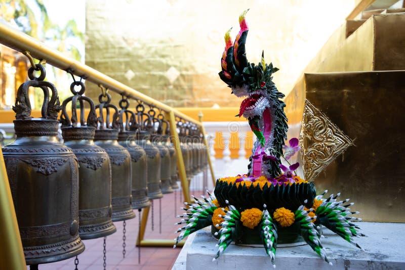 Vista próxima de um Krathong feito a mão e de uns sinos alinhados do ferro em um templo tailandês imagens de stock