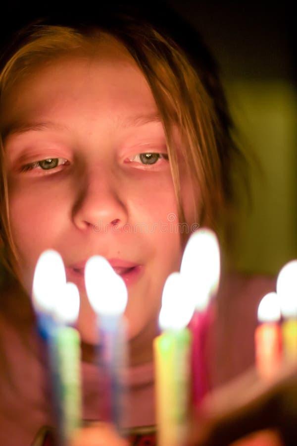Vista próxima na criança que olha em velas no bolo de aniversário imagens de stock