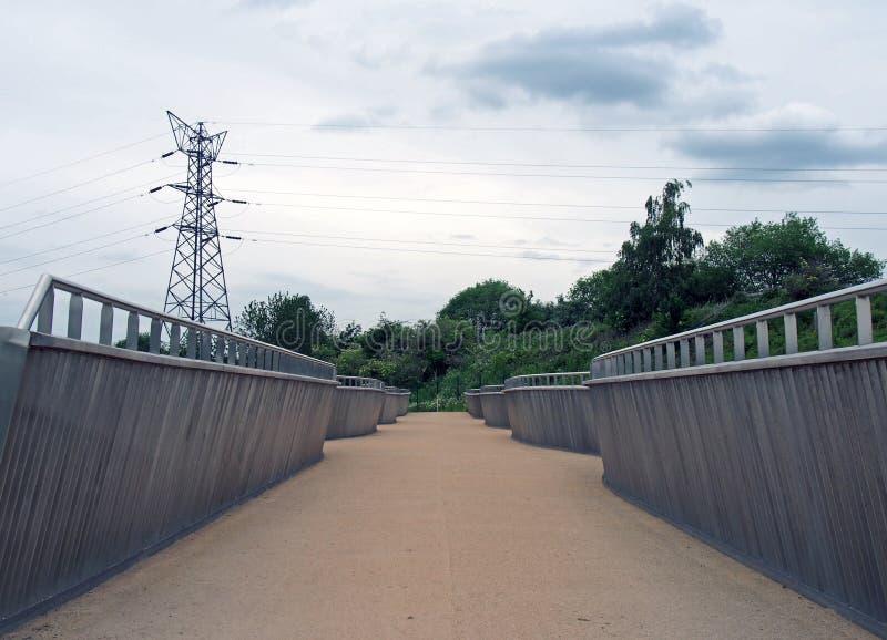 Vista prospettica della passerella pedonale che attraversa l'ambo sul fiume a knostrop Leeds con i piloni elettrici fotografia stock